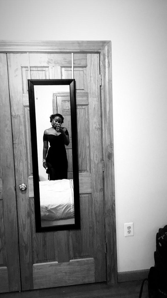 Black and white image of a dark-skinned black woman (it is I, the author of this blog) taking a mirror selfie from the far side of the bed, so that a bit of the bed spread is visible in the mirror as is the door on which the slim black-framed mirror hangs. The woman wears a black off-the-shoulder dress. The image is blurry, so you can't tell that she has been crying.