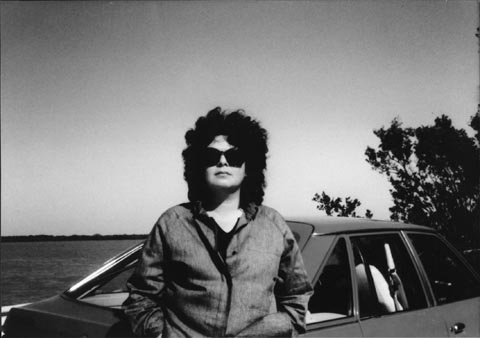 Black and white image of a light-skinned black woman with an 80's feathered haircut. She's standing in front of a car and wearing a pair of large sunglasses and a zipped up jacket with her hands in her pockets. There are some trees behind the car to the right of the image and what looks to be a body of water in the background.