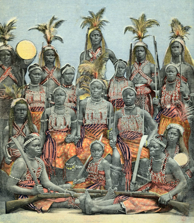 In what looks to be a colorized tintype image, there are four rows of dark-skinned black women and girls. Each row has four people, with the first row seated on the ground, the second seated higher up, and the final two standing. They are all wearing red tops covered in white beads, some worn like tank tops and others crisscrossed over the chest in an x shape. The back row of women are wearing feathered headdresses.