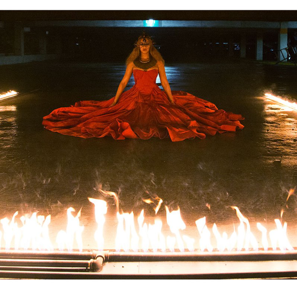 Image of a light-skinned black woman (Beyoncé) seated on the ground and wearing a red gown spread around her. A line of fire burns in the foreground and extends backwards on either side of the woman in two parallel straight lines. The pillars in the background give the impression that this scene is unfolding in a parking structure.